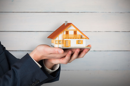 homeowner: Businessman holding miniature house model against painted blue wooden planks
