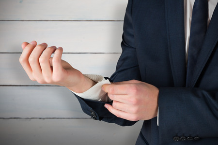 cuffs: Businessman adjusting his cuffs on shirt against painted blue wooden planks Stock Photo