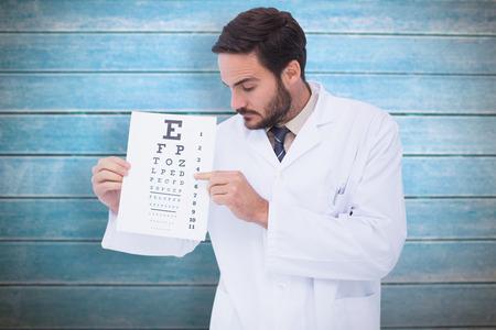 bata de laboratorio: Doctor en bata de laboratorio que muestran prueba de los ojos contra los tablones de madera