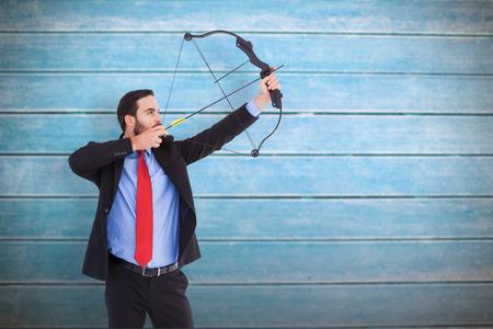 arco y flecha: Hombre de negocios enfocada disparar un arco y flecha contra tablas de madera