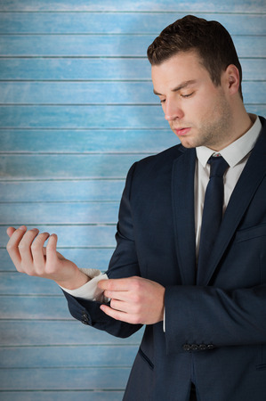 cuffs: Businessman adjusting his cuffs on shirt against wooden planks Stock Photo