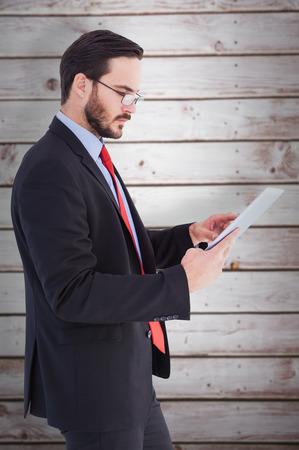 scrolling: Businessman scrolling on his digital tablet against wooden planks