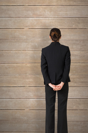 hands behind back: Businesswoman standing with hands behind back against wooden planks