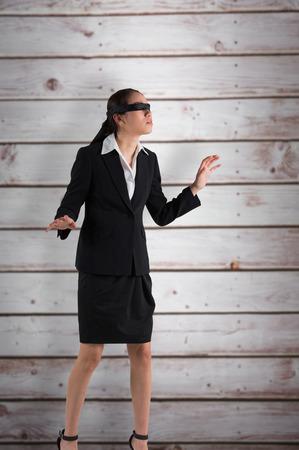 ojos vendados: Empresaria con los ojos vendados con las manos en contra de tablones de madera