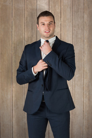 tightening: Businessman tightening his tie against wooden surface with planks Stock Photo