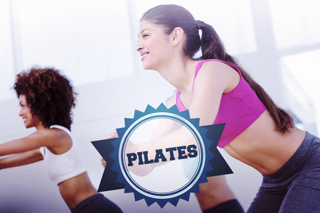 pilates studio: The word pilates and cheerful fitness class doing pilates exercise against badge
