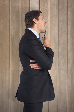 Thinking businessman holding pen against wooden surface with planks photo