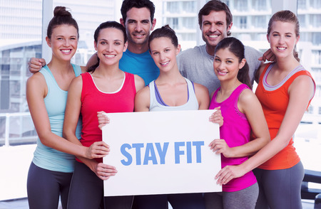 The word stay fit against fit smiling people holding blank board Stock Photo