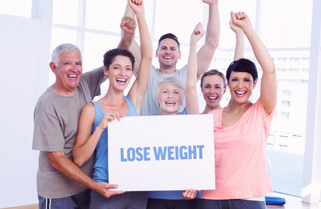 The word lose weight against portrait of happy fit people holding blank board