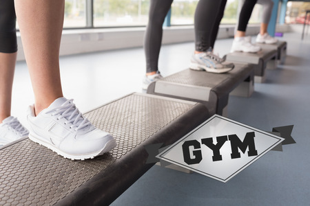 stepping: The word gym and womens feet stepping in aerobics class against badge Stock Photo