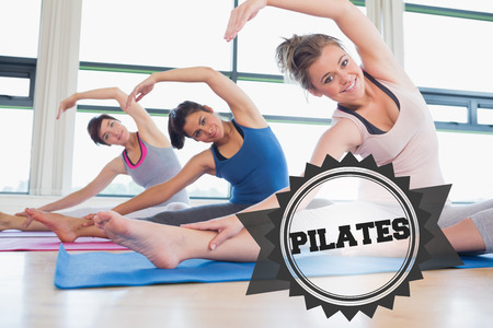 pilates studio: The word pilates and women stretching at yoga class against badge Stock Photo