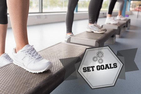 tied hair: The word set goals and womens feet stepping in aerobics class against hexagon