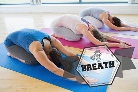 childs: The word breath and women doing childs pose in yoga class against hexagon Stock Photo