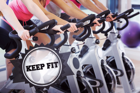 keep fit: The word keep fit and mid section of people working out at spinning class against badge Stock Photo