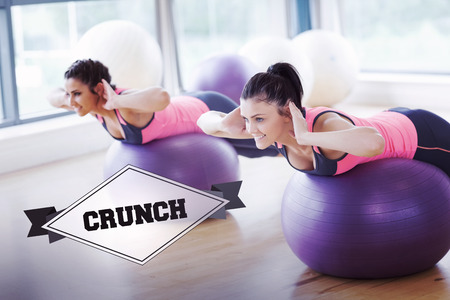 crunch: The word crunch and two fit women exercising on fitness balls in gym against badge