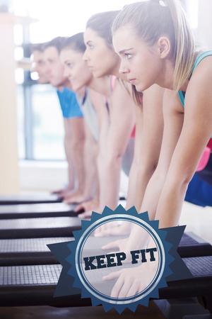 keep fit: The word keep fit and instructor with fitness class performing step aerobics exercise against badge