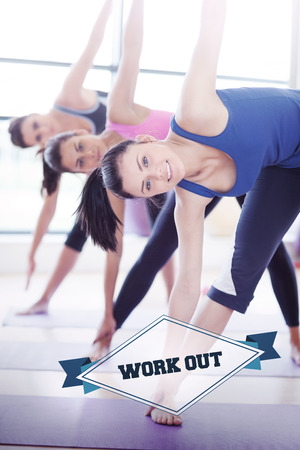work out: The word work out and class doing stretching pilate exercises in fitness studio against badge