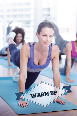 warm up: The word warm up and women doing stretching exercises in fitness studio against badge Stock Photo