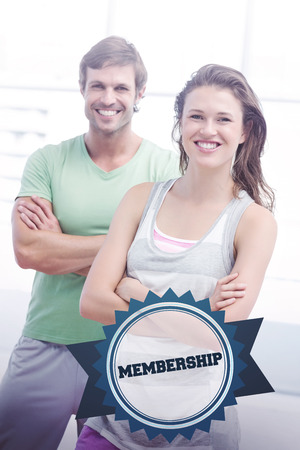exercise room: The word membership and portrait of a fit couple with arms crossed in exercise room against badge