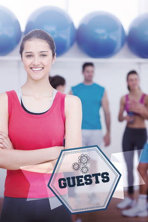 The word guests and smiling woman with friends in background at fitness studio against hexagon photo