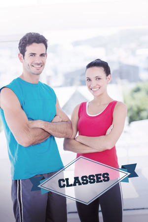 exercise room: The word classes and fit couple with arms crossed in bright exercise room against badge Stock Photo