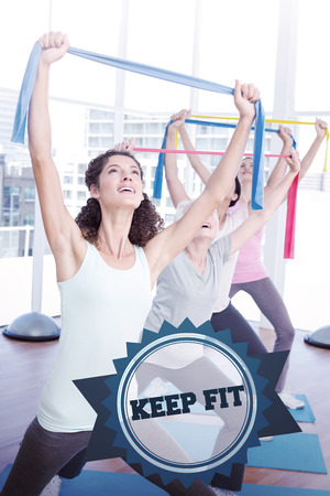 keep fit: The word keep fit and class holding up exercise belts at yoga class against badge