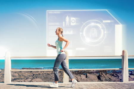 mature woman: Fit mature woman jogging on the pier against fitness interface Stock Photo
