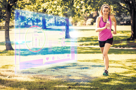 woman looking down: Fit blonde jogging in the park against fitness interface