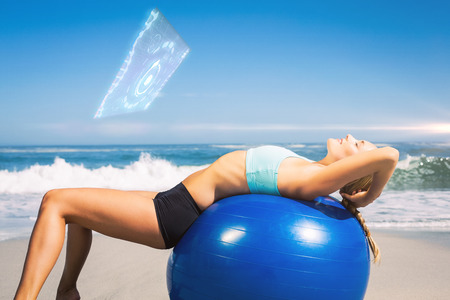ball stretching: Fit woman lying on exercise ball at the beach stretching against fitness interface