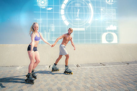 promenade: Fit couple rollerblading together on the promenade  against fitness interface Stock Photo