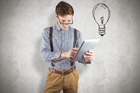 Geeky businessman using his tablet pc against white background photo