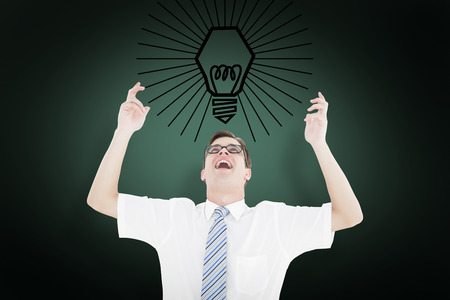 Geeky happy businessman with arms up against green background with vignette photo