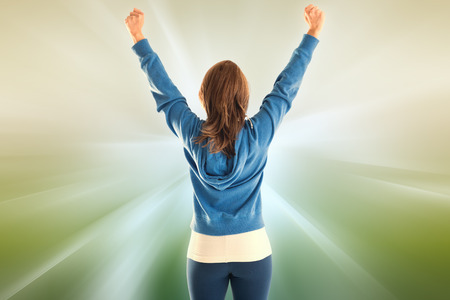 Cheering fit woman against abstract background