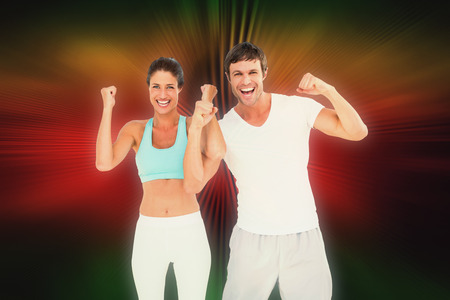 clenching fists: Cheerful fit couple clenching fists against abstract background Stock Photo