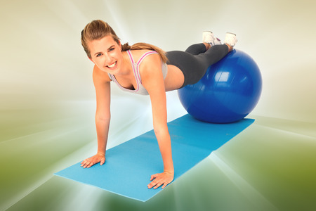 ball stretching: Portrait of a fit woman stretching on fitness ball against abstract background