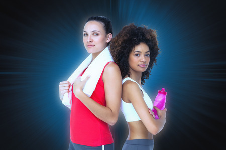 fit women: Fit women standing with waterbottle and towel against abstract background Stock Photo