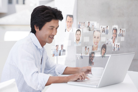 mature business man: Happy man using laptop while having a coffee against business people Stock Photo