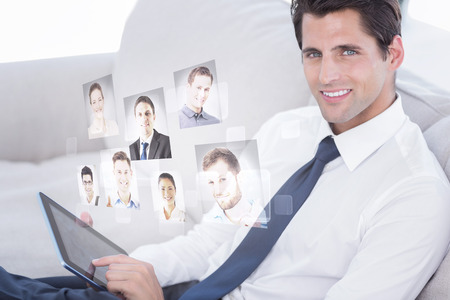 Smiling businessman using digital tablet against profile pictures photo