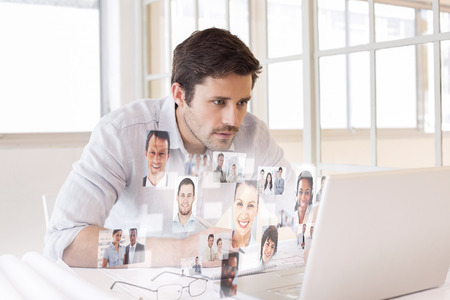 Businessman working on blueprints and laptop in office against business people photo