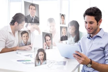 Uomo d'affari attraente utilizzando una tavoletta al lavoro contro immagini del profilo Archivio Fotografico - 44787425