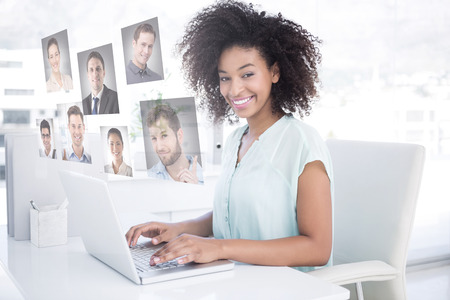 Happy businesswoman working on her laptop against profile pictures photo