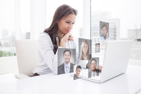 Happy businesswoman using laptop at her desk against profile pictures photo