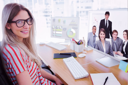 Attractive photo editor working on computer against happy business group having a meeting Imagens