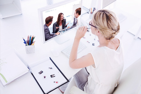 Female photo editor working on computer against attractive businesswoman laughing with her team photo