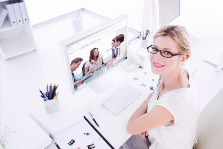 Female photo editor working on computer against glad businesswoman talking to her team Stock Photo
