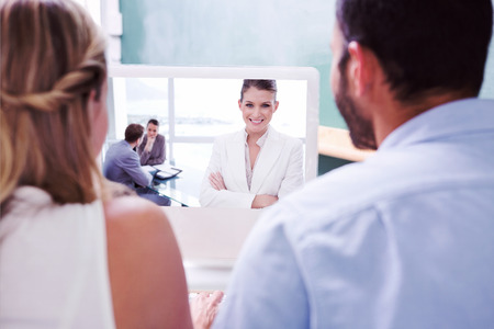 Colleagues looking at computer against smiling marketing manager standing in conference room photo