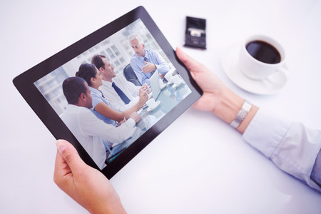 Man using tablet pc against group of business people brainstorming together photo