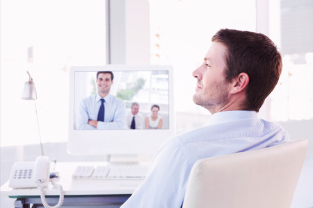 Smiling businessman sitting at his desk  against cheerful businessman posing while his colleagues are working photo