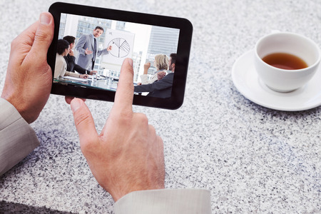 Businessman using small tablet at table against business people in office at presentation photo
