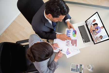 international sales: International business associates in a meeting against sales persons studying statistics Stock Photo